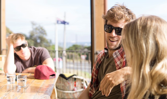 couple talking with a man on the background
