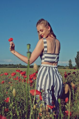 woman wearing striped pants surrounded by flowers