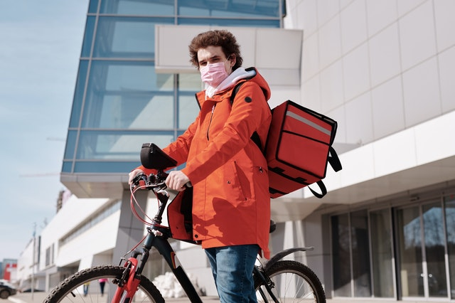 delivery man wearing a face mask and riding a bicycle