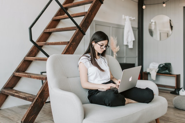 woman using laptop and earphones at home