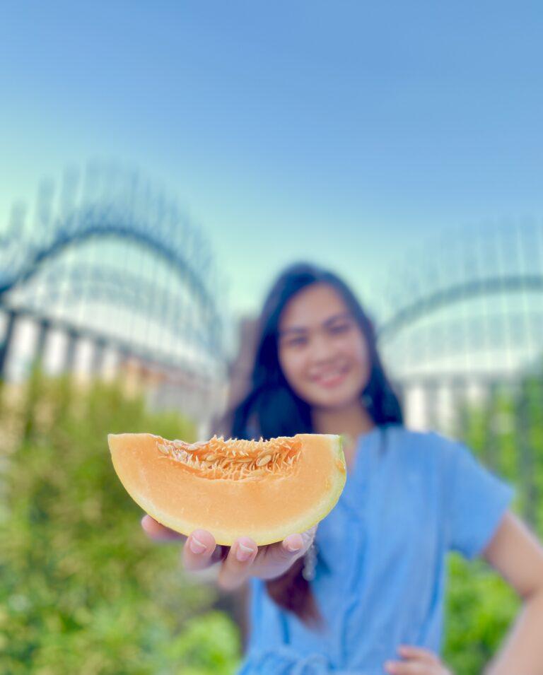 Ragazza sorridente,tiene melone in mano,celo azzurro