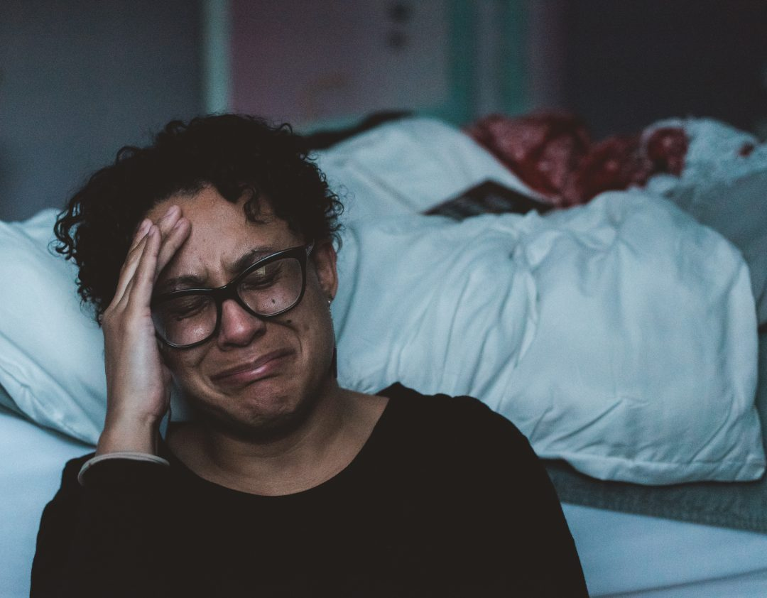 Crying woman sitting on floor next to bed. No sunlight in her life.