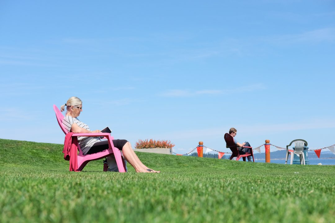 People in chairs taking sun outside on a field of grass.