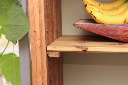 Hyllplan på hemsnickrad kökshylla. I hyllan syns ett gammalt träkärl som används som fruktfat.