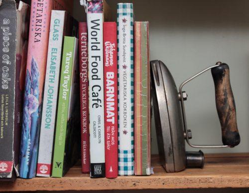 Kokböcker som står i en hylla med ett strykjärn som bokstöd.