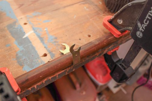 En nyckel sitter runt en rundstav som är fastsatt i snickarbänken med limtvingar.