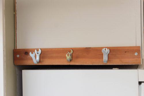En kroklist sitter på ett skåp ovanför kylen. Krokarna är gjorda av små skiftnycklar.