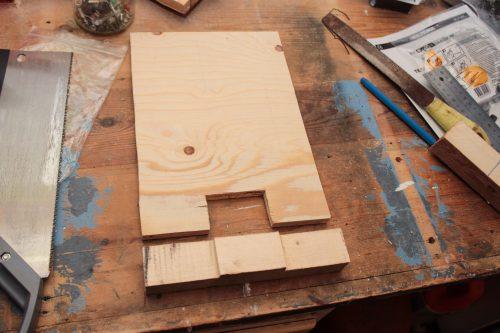 Plywood med hål i mitten och en bottenbit med en utstickande del i mitten. Så fogar du samman ditt flyttbara ställ för torkdukar.