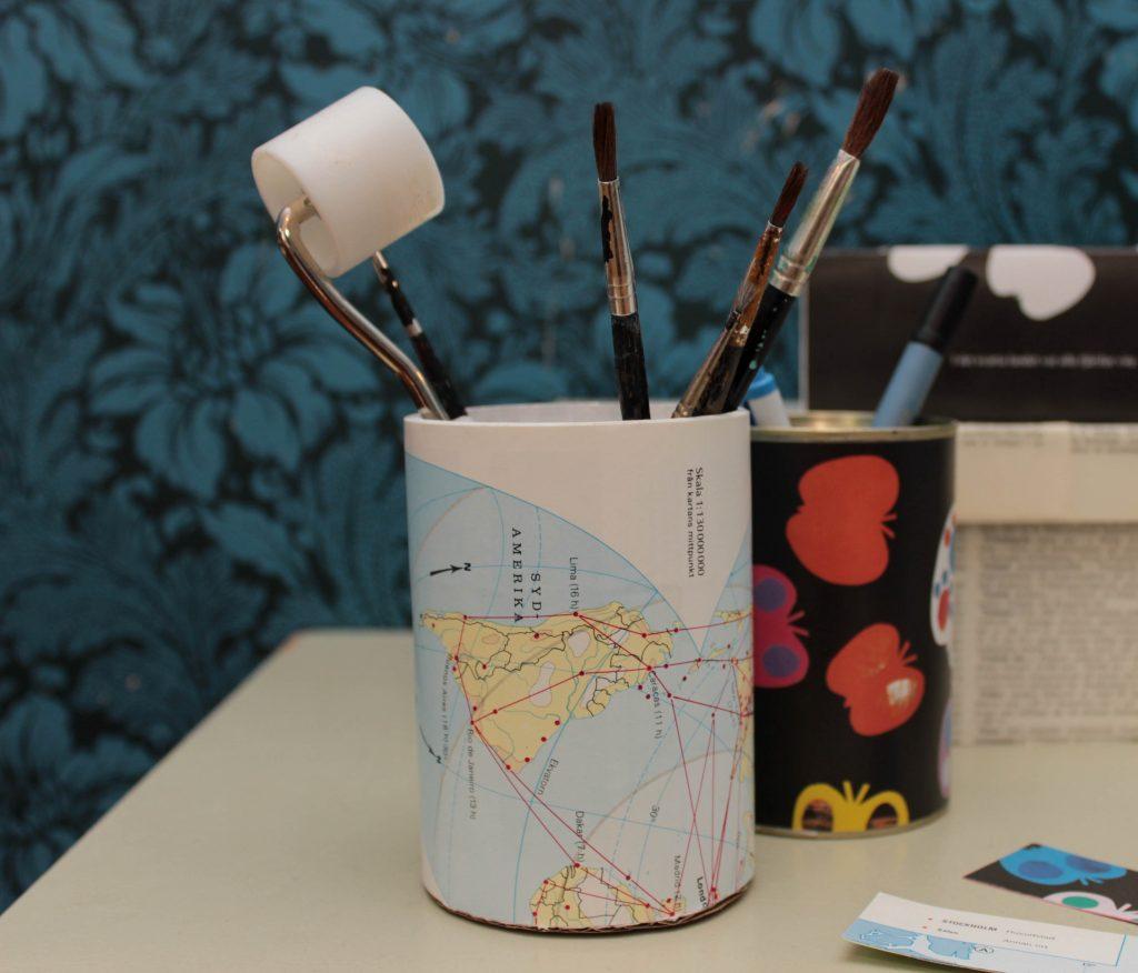 Återbrukade burkar som blivit fin förvaring för pennor med hjälp av gamla boksidor.
