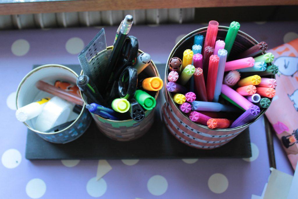 Pennförvaringen sedd uppifrån med de tre burkarna fyllda med sudd, lim, pennor, tuschpennor, sax och linjal.