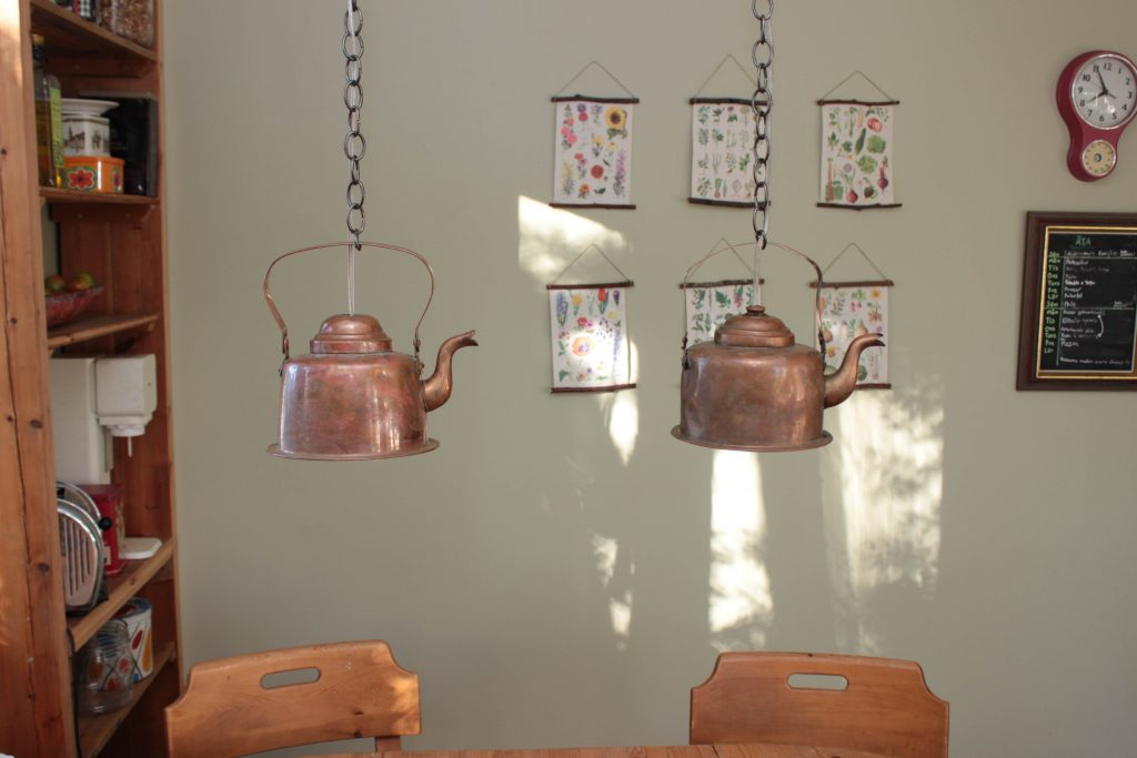 Två kopparkaffekannor hänger som lampor över ett köksbord.