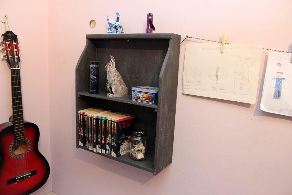 Gråmålad lådhylla fylld med pocketböcker och småsaker.