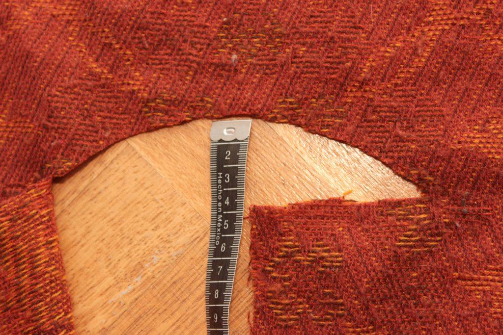 Måttband som visar 4 cm i mitten på ett halvmåneformat halshål.