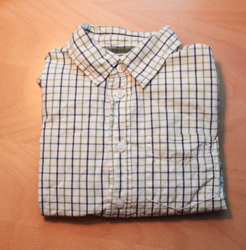En barnskjorta som är vit med randiga streck.