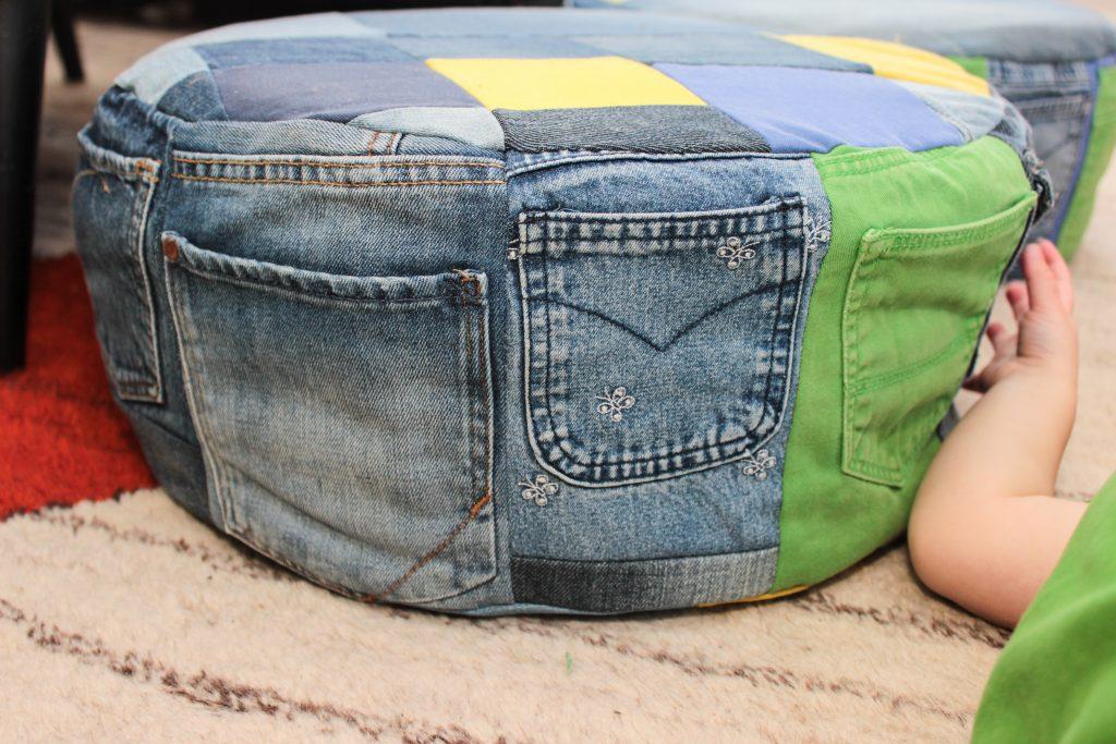 Kanten på sittpuff av jeans som består av jeansfickor.
