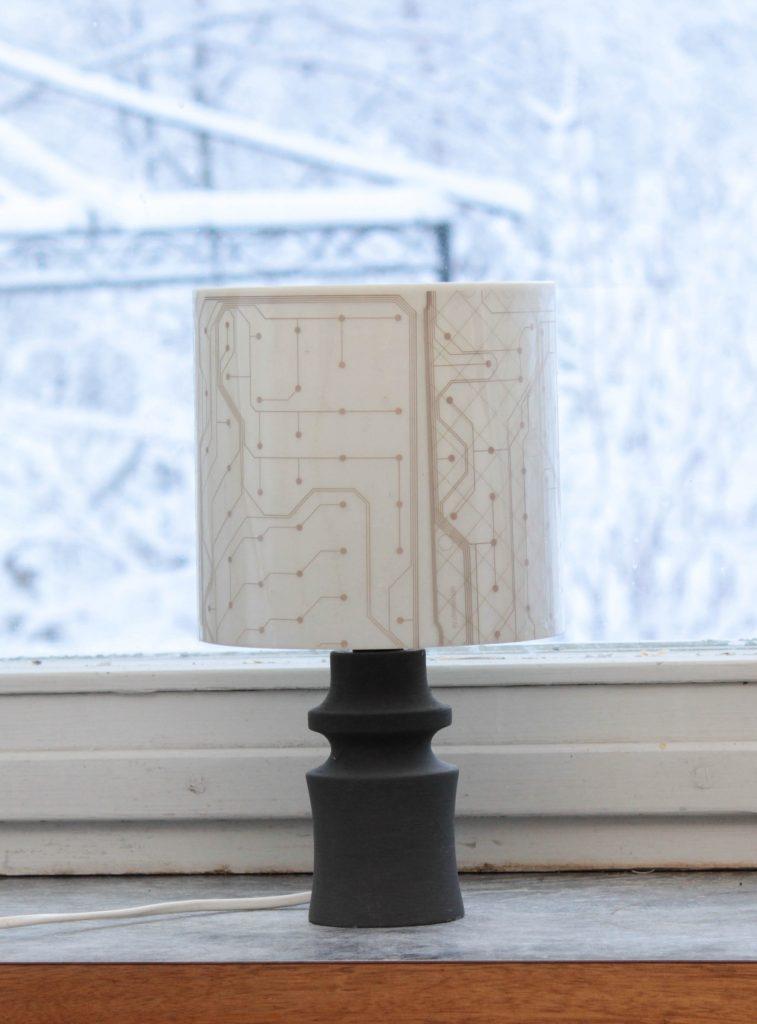 Lampskärm av kretskort där den genomskinliga kretskortssfilmen från tangentbordet har klistrats på en cylinderformad lampskärm.