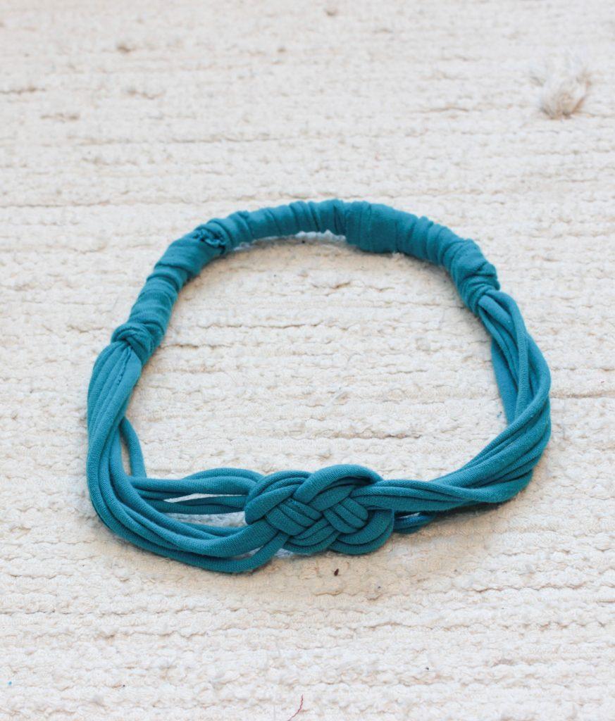 Turkosblått hårband av t-shirt med en snygg knut längst upp.