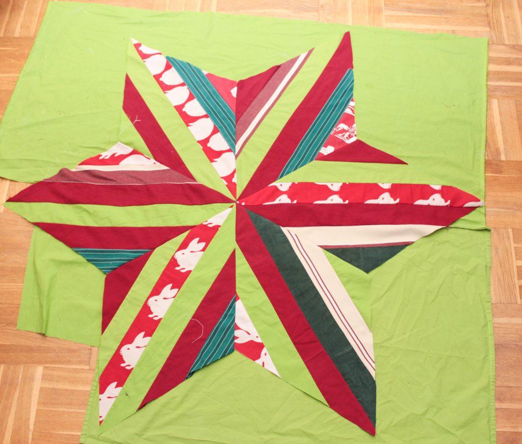 Stjärnformad julgransmatta på ett grönt bottentyg.