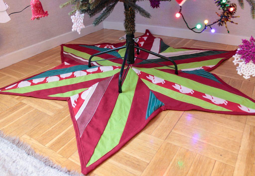 Stjärnformad julgransmatta i grönt och rött under julgransfoten.