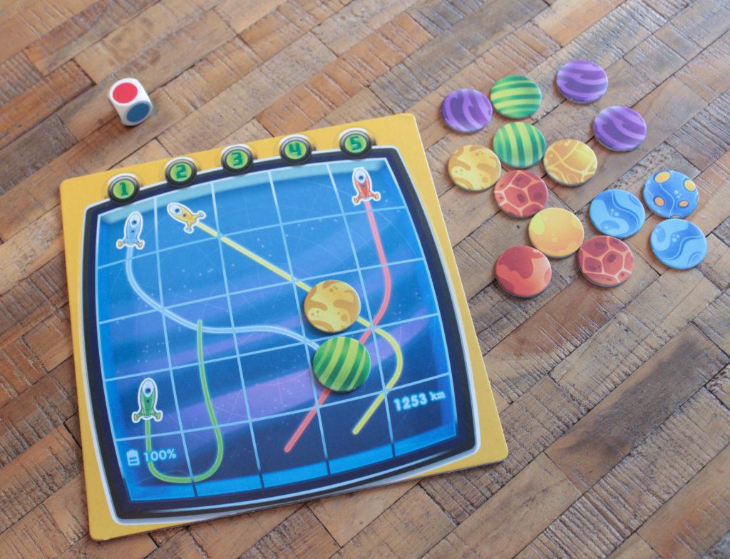 Rymdspel med markörer, spelplan och tärning.