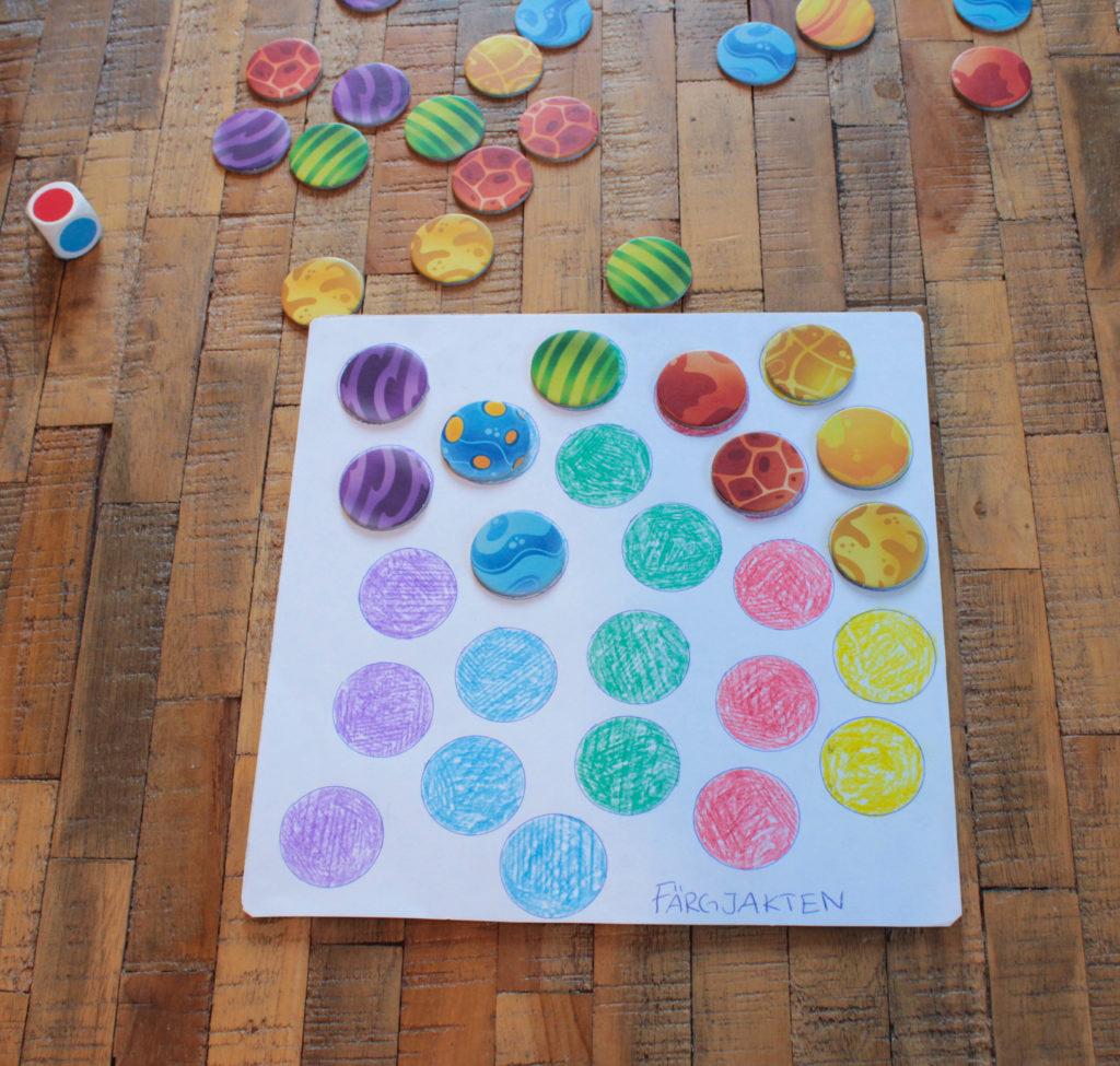 Färgjakten med spelplan, markörer och färgtärning. Enkla cirklar som färglagts med kritor.