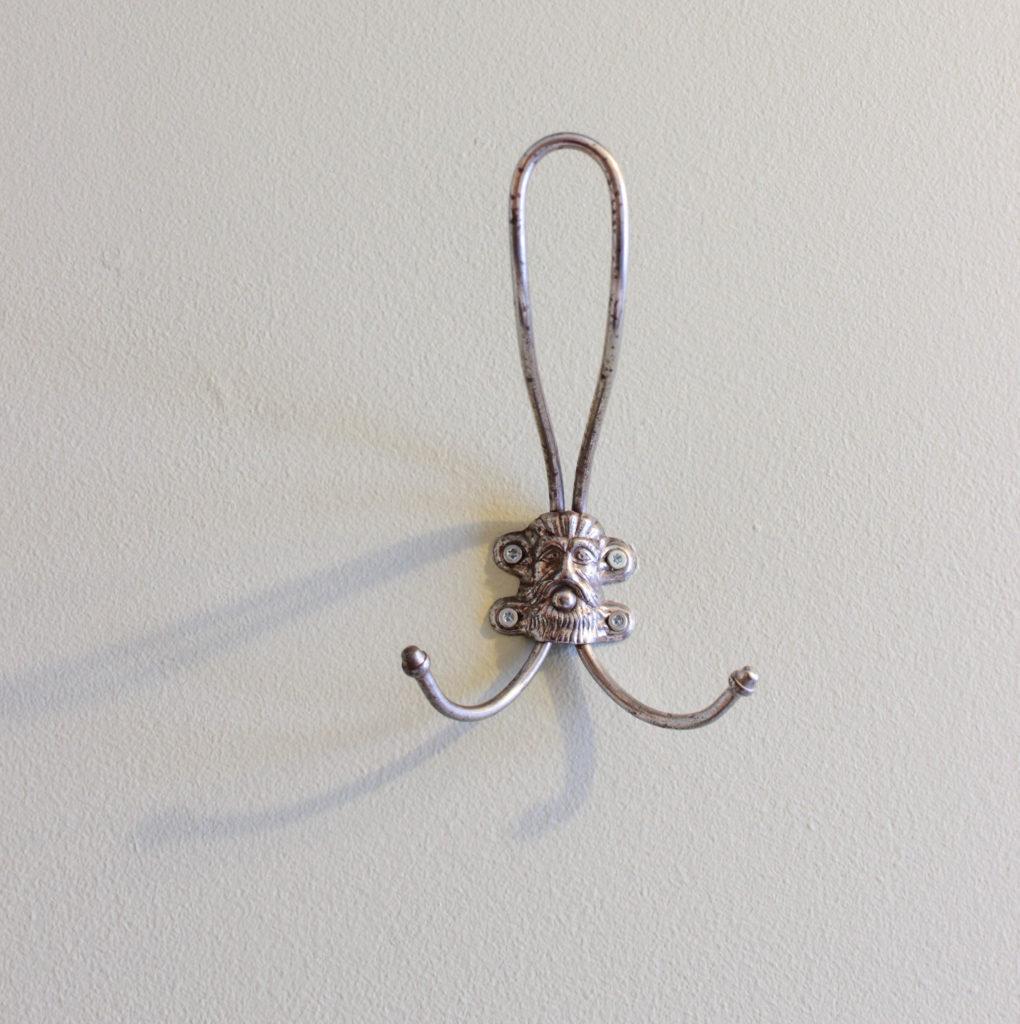 Närbild på en krok med ett hårigt mansansikte på. Kroken har en hattkrok och två klädkrokar.