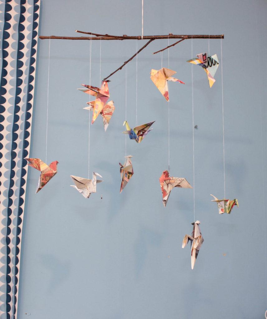 Origami fåglar som hänger i en mobil.