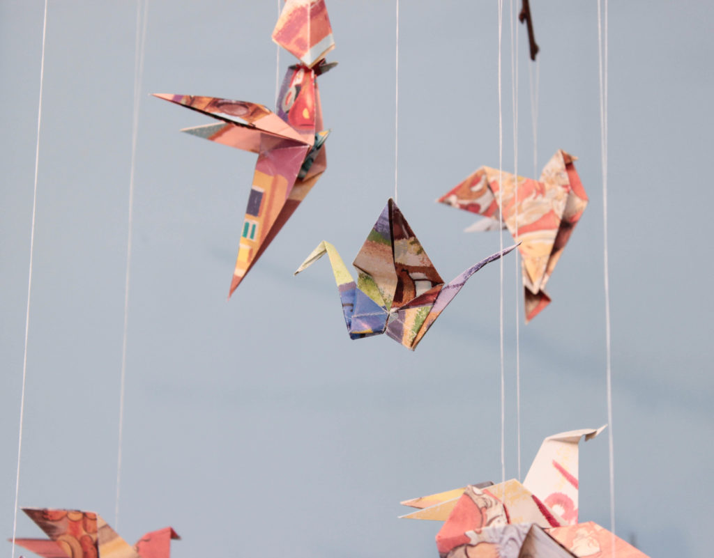 Många origami fåglar som hänger i en mobil.