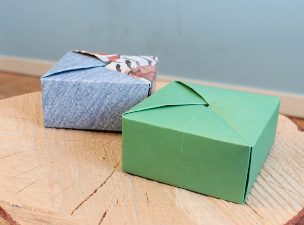 Självförslutande presentaskar i origami. En är grön och en annan blå med lite tomtar på.