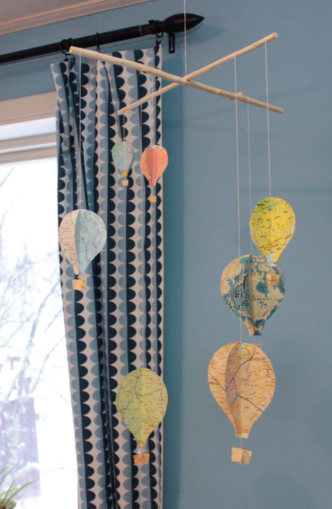 Luftballonger som hänger i en mobil gjorda av kartor i olika färger.