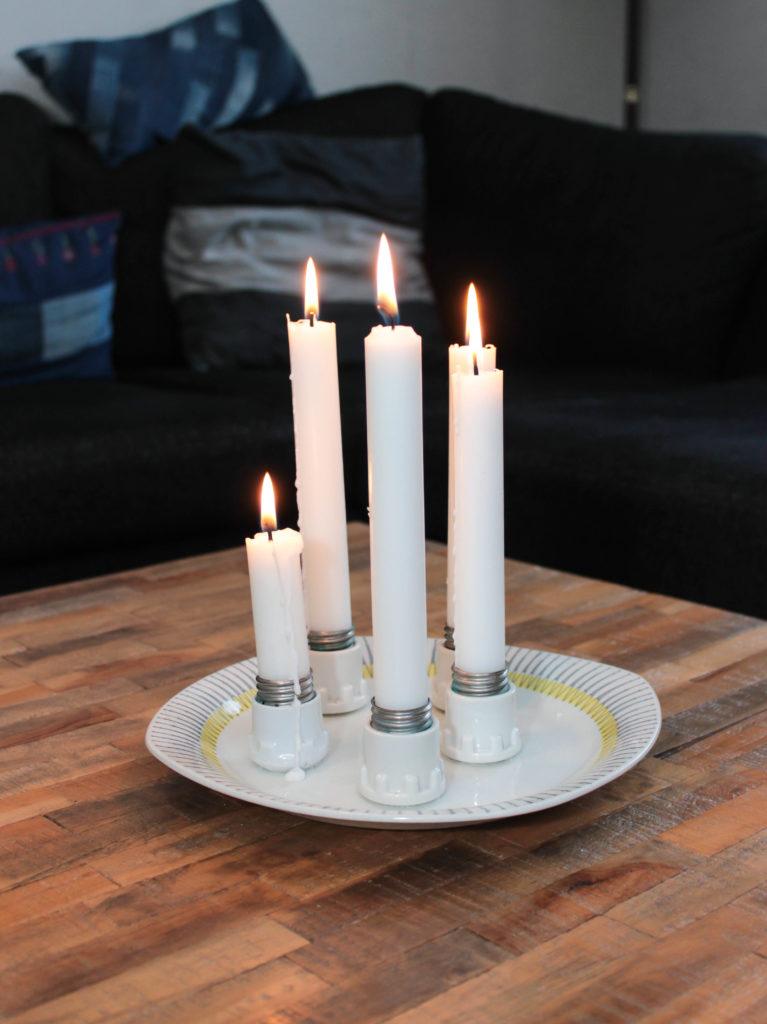 Ljusstake där 5 säkringar limmats fast på en tallrik. Bilden visar när ljusen lyser.