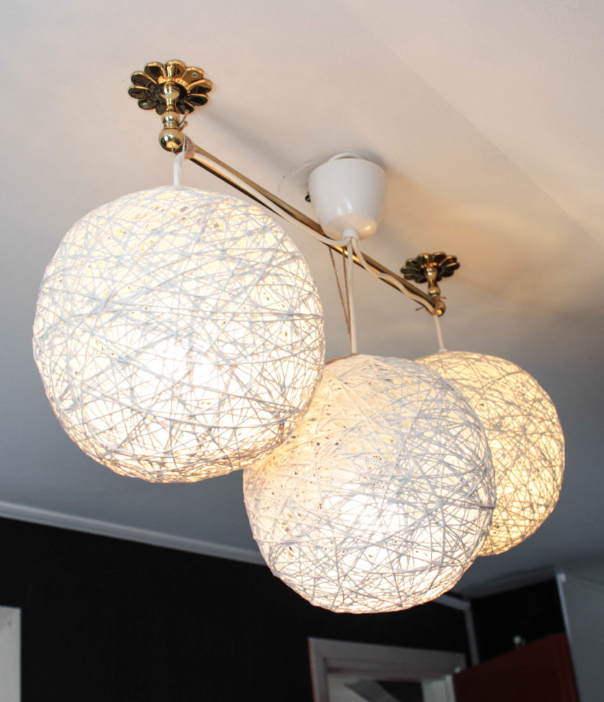 Tre planetlampor hänger tillsammans på en stång i taket.