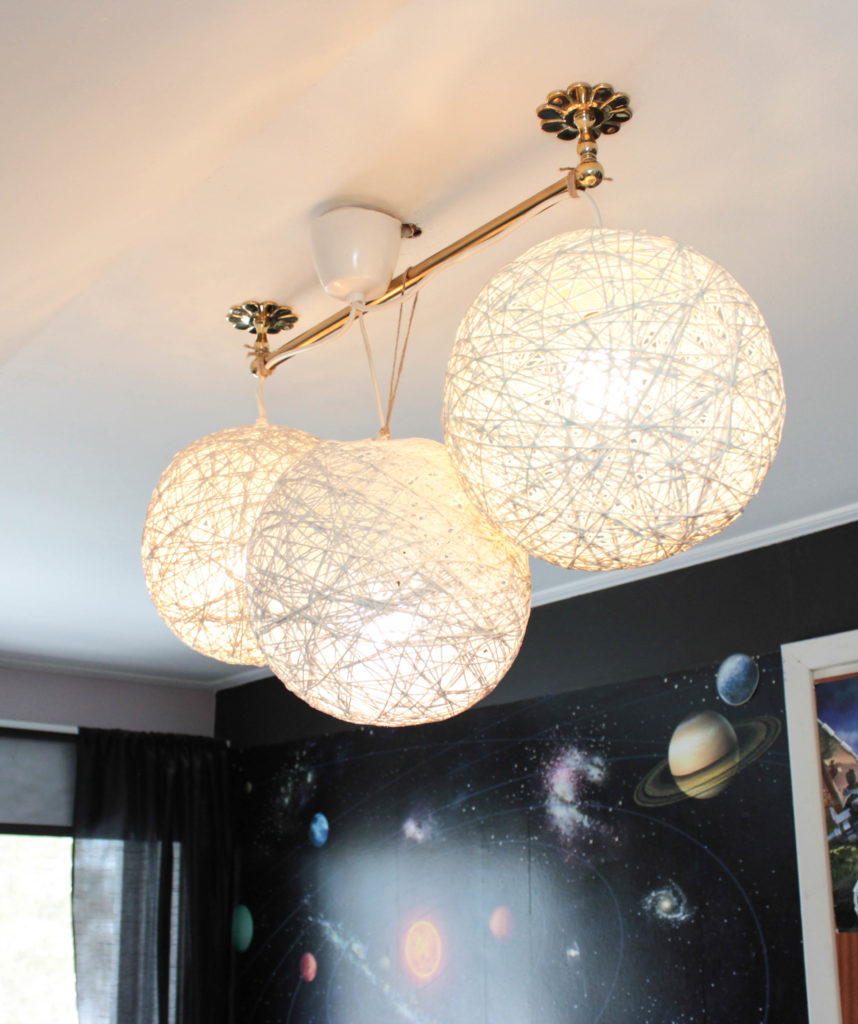Tre planetlampor hänger från taket med en tapet med solsystemet på i bakgrunden.