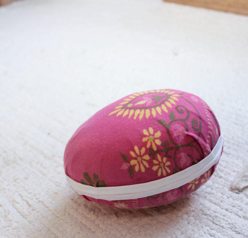 Ett rosa påskägg med tyg och en vit bomullskant.