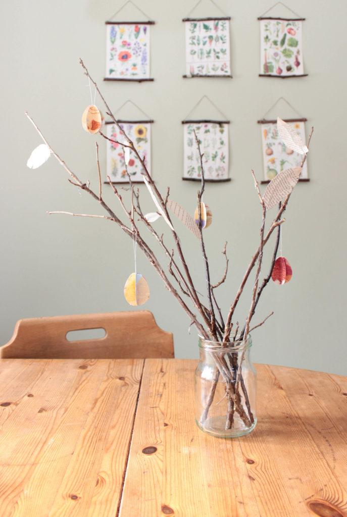 Påskris dekorerat med pappersägg och bokfjädrar. Gör enkla dekorationer till ditt påskris.