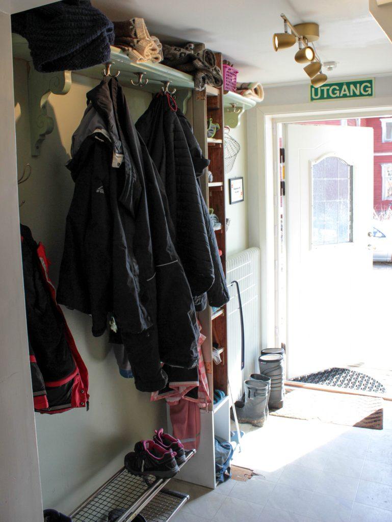 Hallen från andra hållet med klädhängare, skförvaring och förvaringshylla.
