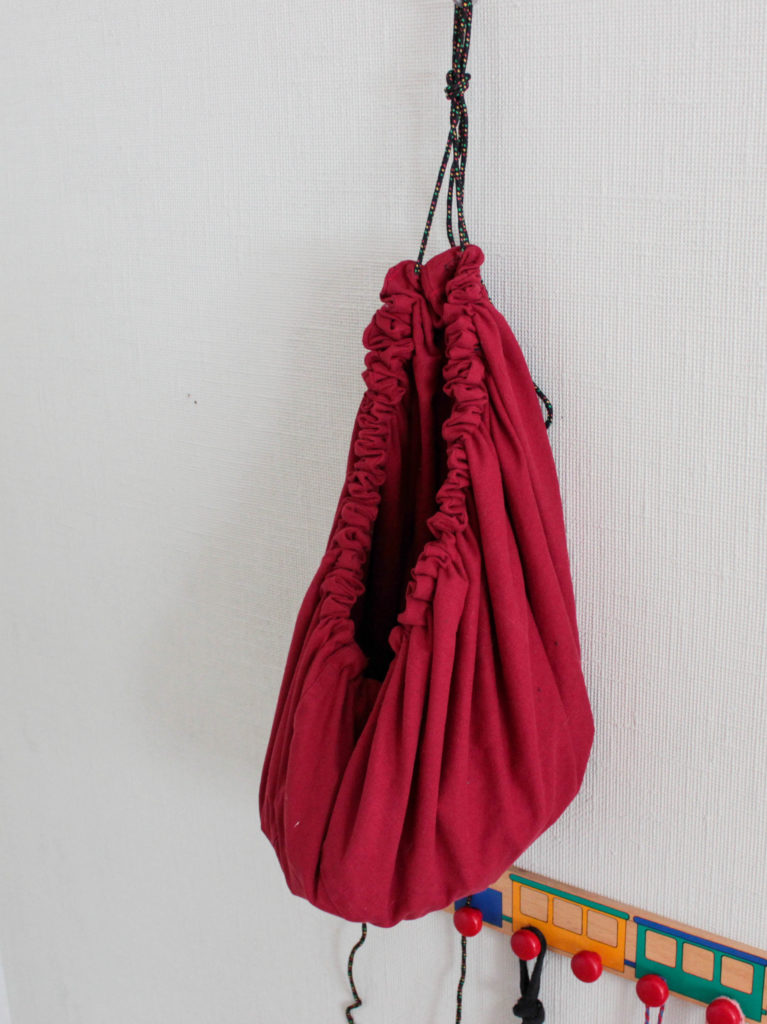 Klossförvaring när den dragits ihop till en säck och hänger på väggen.
