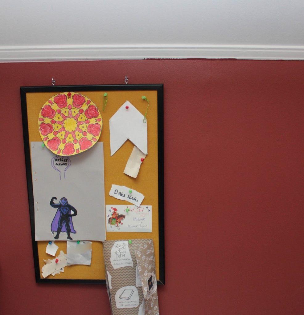 Röd färg på väggen i ett barnrum för ett mellanstadiebarn.