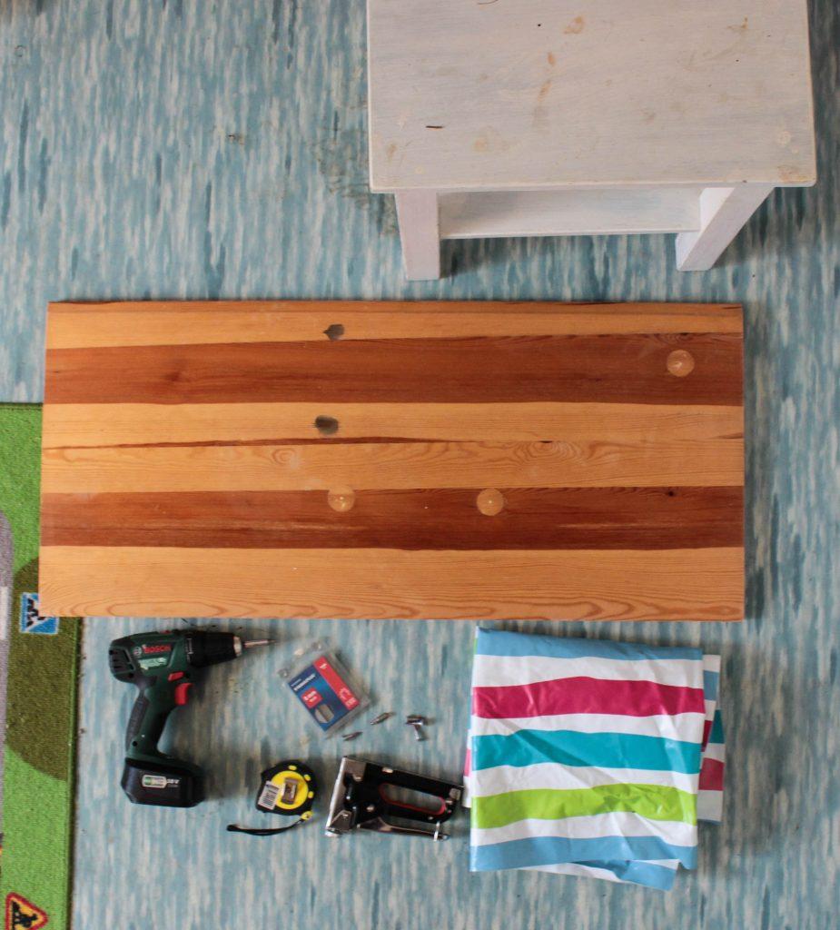 Det du behöver för att göra ett större lekbord: skiva, pall, vaxduk och verktyg.