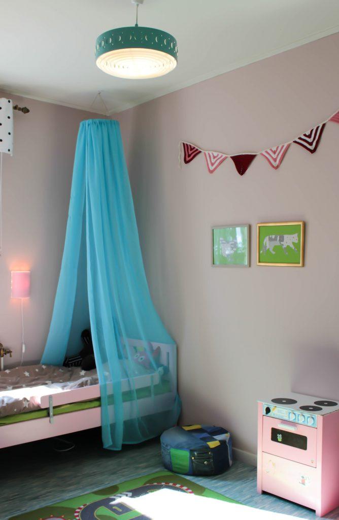 Inredning i ett barnrum med en DIY sänghimmel över sängen.