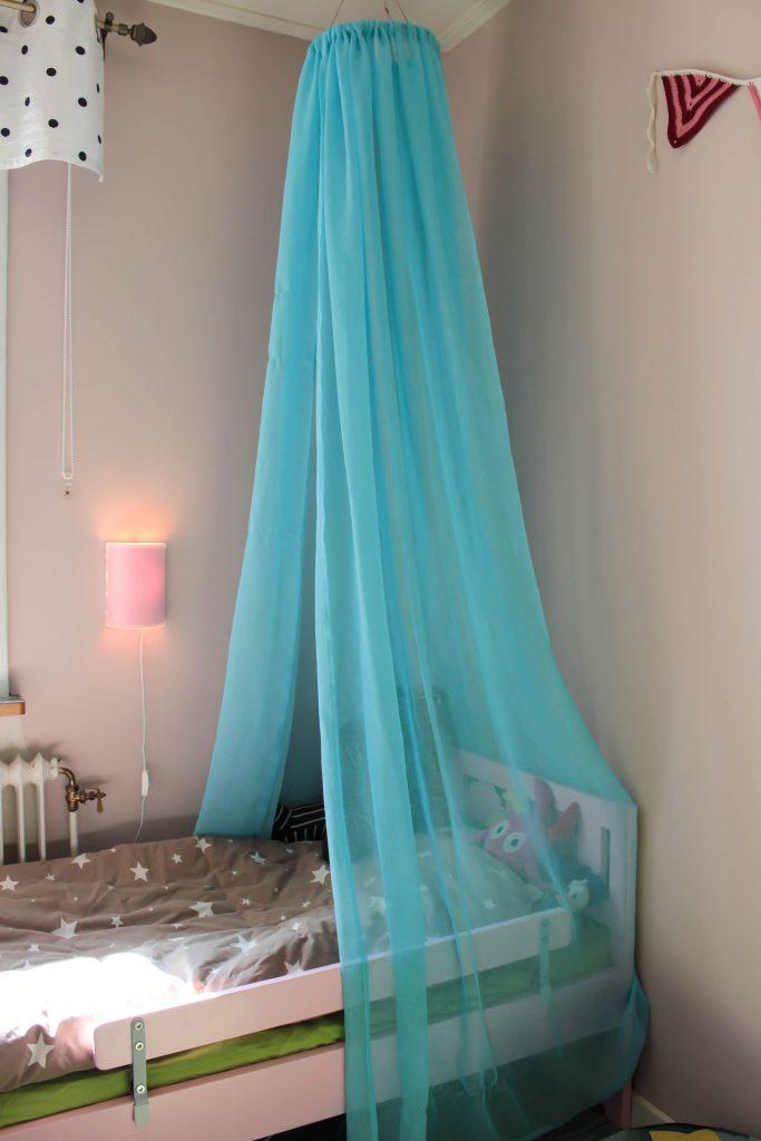 Blå sänghimmel ovanför en rosa säng.