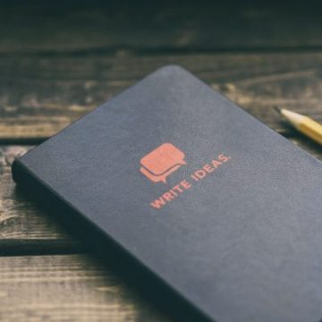 Write Ideas, picture shows a black booklet and a pen on a wooden table