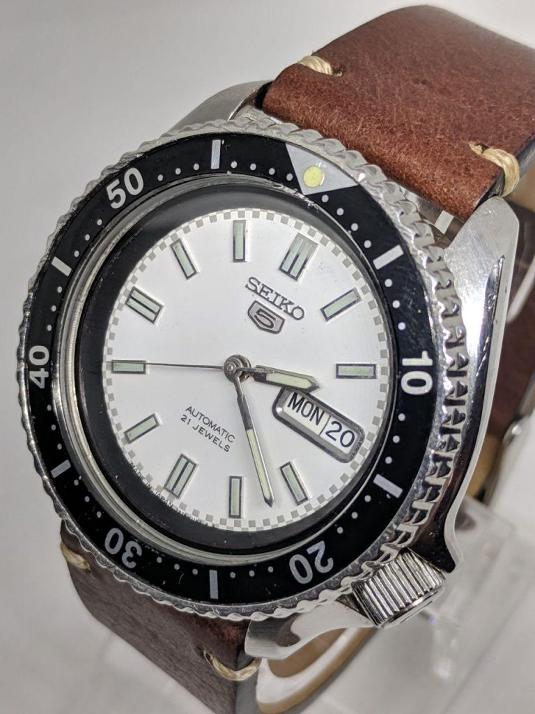 Seiko Mod by WellingTime UK. Seiko SKX White Reace Mod: stainlees steel Seiko SKX watch with a white dial with raised and polished hour markers topped with lume the minute markers are grey on the edge of the watch dial.  The dial is surrounded by a black chapter rings with no markings.  Pencil style hands with original seiko Bezel and insert complete with a vintage leather strap 2 peice with stainless steel buckle.