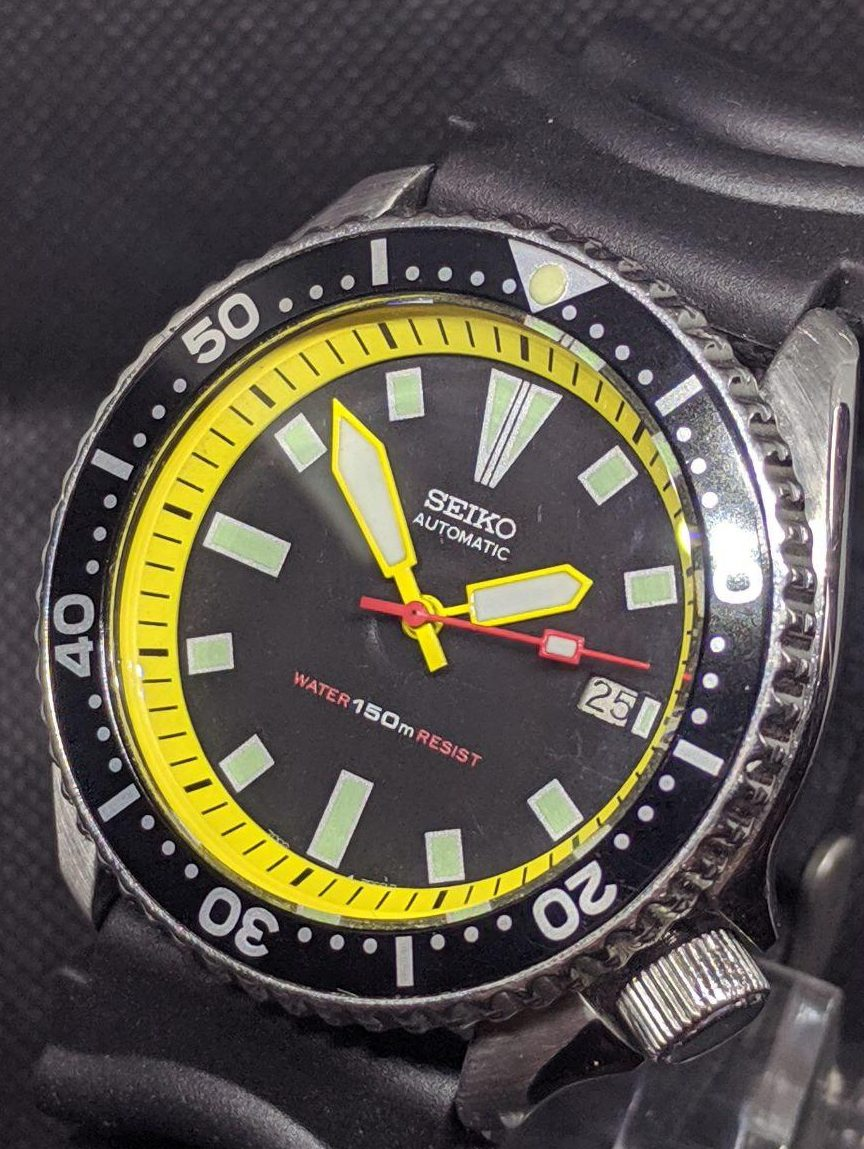 """Seiko Mod by WellingTime UK. Seiko 7002 Ploop Colours Mod. This modification has retain the ogianl style dial and added a bit of colur through the addition of a yellow chapter ring with black minute markers. The chapter ring mates the Yellow hour and minute hand on this seiko watch. The red ish pink second hand is a very close colour to the lower text on the dial """"150m water resist"""" tieing this vintage seiko mod together beautifully.Fitted with a new Z22 Strap with satin finished buckle (2 peice strap)"""
