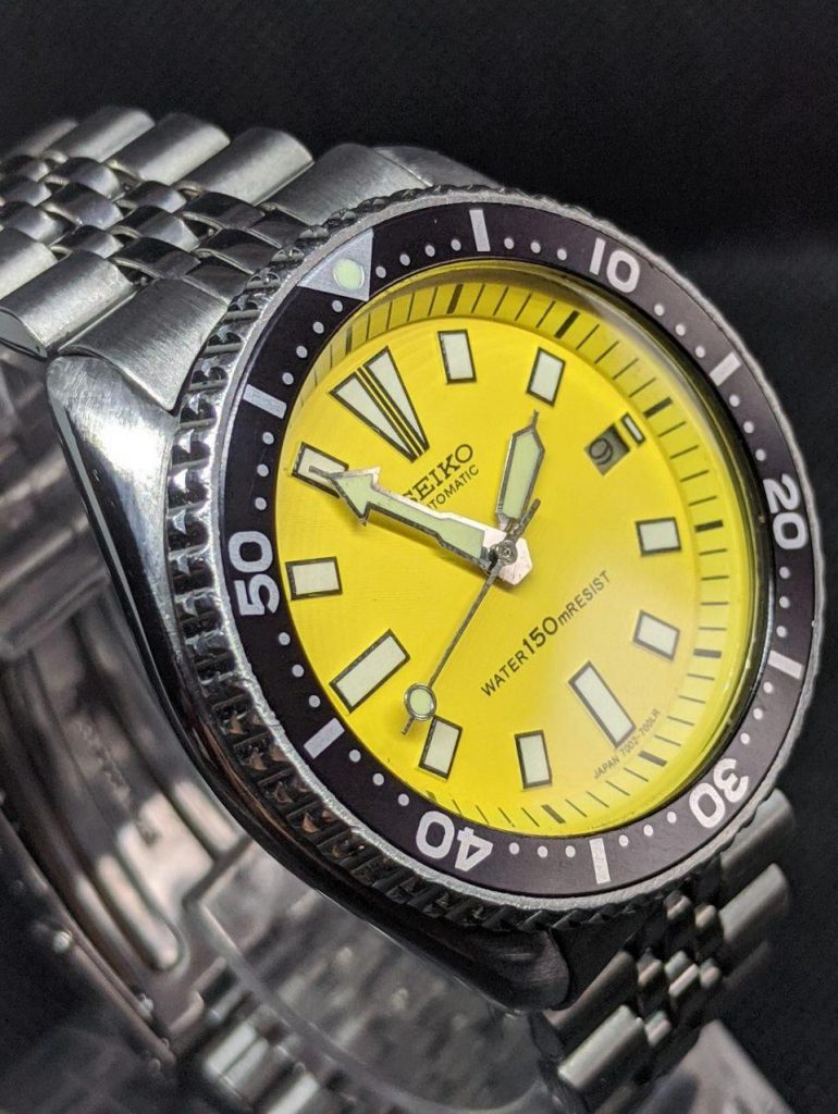 Seiko Mod by WellingTime UK. Seiko 7002 vintage watch revival mod: This watch was modded to be your summer watch the dial and chapter ring in a vibrant yellow with black print. the hour marker are lume'd along with the polished stainless steel vintage seiko diver hands topped with a lolly pop second hand.The original stainless steel case and bezel have been retained and fitted with a new Seiko hardlex crystal, Genuine black replacement Seiko bezel insert and completed with a Seiko stainless steel jubilee bracelet with a brushed and polished appearance
