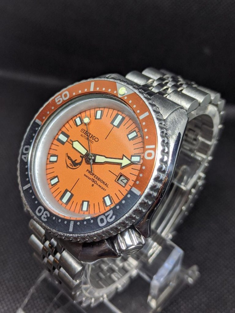 Seiko Mod by WellingTime UK. Seiko 7002 orange SOXAsea monster mod: The original stainless steel case bezel and bracelet have been retained and fitted with a replacement orange  SOXA dial with a whale printed on the lower left quarter the dail has lumed hour markers and black print which also displays the minute markers. This is surrounded by a  glossy silver chapter ring without minute markings. The hands are polished gold plated steel complete with super bright lume.  The bezel insert is burnt orange and ghost grey tying all the colours together nicely. The crown has been replaced with a S etched Seiko monster style crown to finish up the monster look.