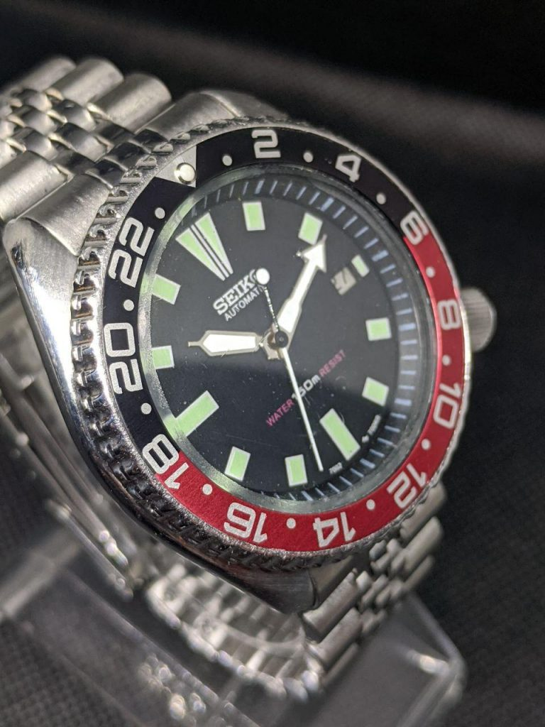 Seiko Mod by WellingTime UK. Seiko 7002 GMT Coke mod. stainless steel seiko Dive watch hasbeen modified to include a GMT bezel insert with 24 hour numerals in a red and black gloss finish and a pearl of lume at noon. The original stainless steel jubilee bracelet is still in use.