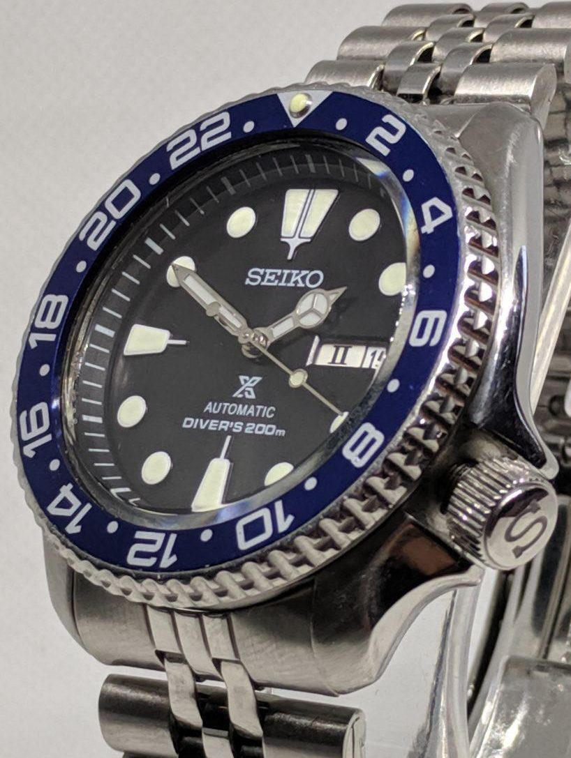 Seiko Mod by WellingTime UK. Seiko SKX007 Prospex Mod: Black Prospex dial with C3 lume, . polished Mercedes  hands, navy blue GMT bezel insert, flat beveled edge sapphire crystal and an S signed / etched crown. The watch sits on a Seiko Jubilee Bracelet.