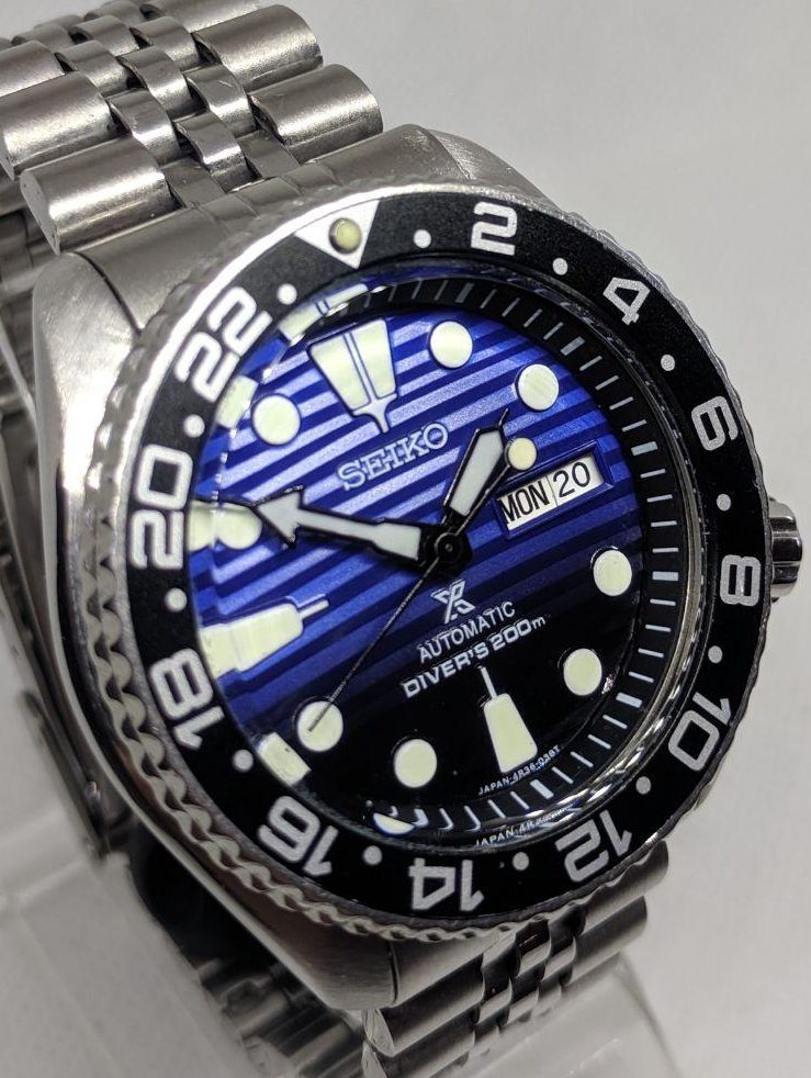 Seiko Mod by WellingTime UK. Seiko SKX007  Prospex Mod: Save the Oceans dial with black to blue faded colour and bright lume, black bezel insert with GMT numbers. Black Seiko SKX hands and a Seiko Jubilee Bracelet.