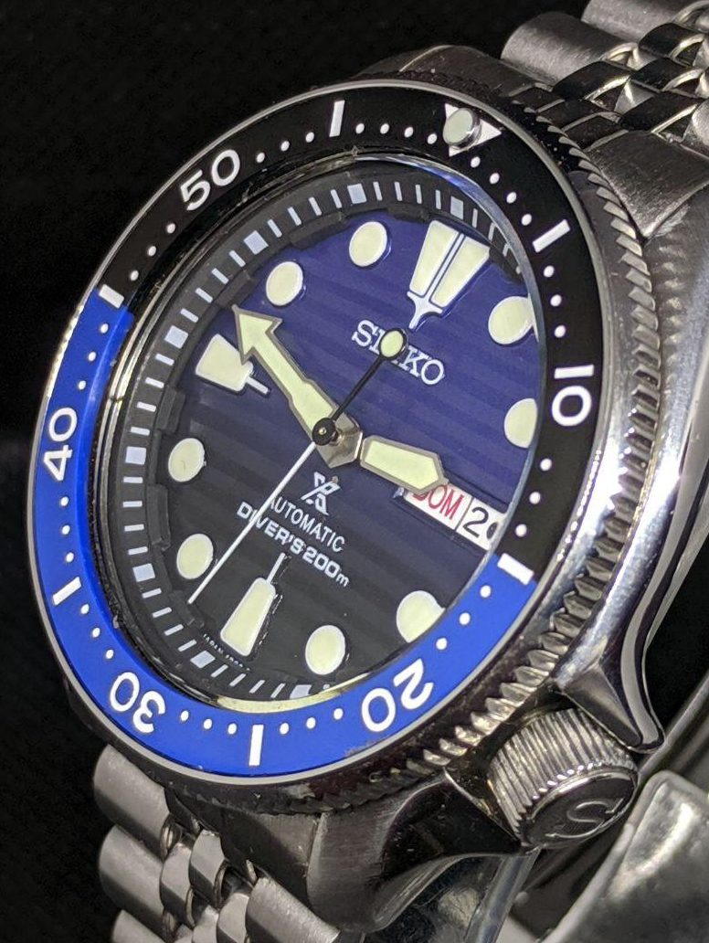 Seiko Mod by WellingTime UK. Batman Submariner SKX Mod: Flat sapphire crystal with blue AR coating, black Tuna chapter ring.  brushed SKX hands with C3 Lume mounted on a seiko Save the Oceans black to blue fade wave dial and Seiko NH36 movement. SKX Coin edge bezel fitted with a flat batman bezel insert black and blue in colour with a pearl of lume at noon. The watch sits on the wrist witha stainless steel seiko jubilee strap